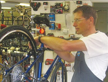 JAMES CHILTON/Miner<br><br> Ran Hanks does maintenance work on a customer's bike at Bicycle Outfitters Friday afternoon. Hanks said he has observed an increasing trend of customers bringing in their bikes for retrofitting or repair.