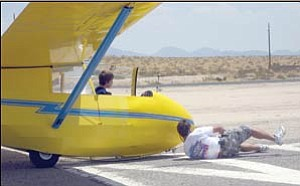 Joseph Sheble looks on as his father Joe clips a towline to the front of his glider. Joseph beat his father's record for the youngest Sheble to fly solo on June 28. He was 14 years old. His father was 16 when he first flew solo.