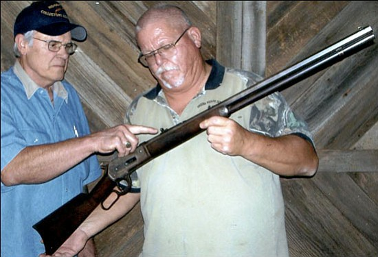 Courtesy <br>Lon Carroll (left) and Don Martin examine a rifle at a recent Mohave Arms Collectors Association meeting.
