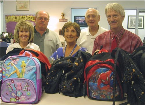 From left, Carol  and Chuck King of Mission Bank, Cerbat Elementary Principal Dawn McGill, Mission Bank President Darrell Lautaret and Cerbat Elementary Assistant Principal Clint Keller pose with backpacks donated by Mission Bank.<br>AARON ROYSTER/Miner