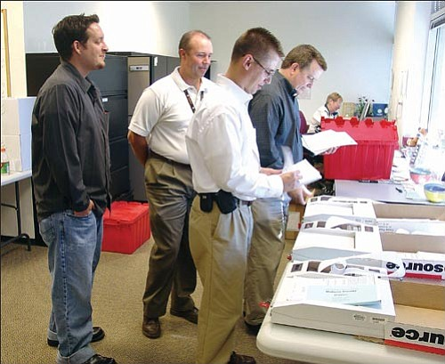Eric Lubliner of Premier Election Solutions (far left) and Mohave County Elections Director Allen Tempert watch as Scott Cancelosi and Craig Stender from the Arizona Secretary of State's Office test Mohave County election equipment on Aug. 21. <br> MOHAVE COUNTY/ Courtesy