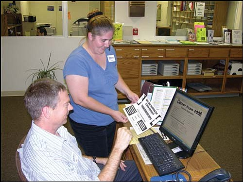 Stacy Arellano (standing) and Don Frerichs, front office clerks at Mohave Community College, review Career Expo 2008 materials as well as the MCC Web site regarding the Expo.<br> MCC/Courtesy