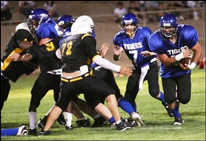 Reggie Jackson (72) was one of four Career Success players ruled ineligible for the Sept. 13 game against KAHS. Jackson closes in on KAHS' Mat Higuera as freshman quarterback Sean Windecker (7) looks on.<br> JEFF MARTIN/Courtesy