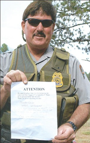 Photo courtesy of Don Martin<br><br>  �You can�t do this!� Paul Krumland, a park ranger for the Grand Canyon-Parashant National Monument, holds the sign that a sportsman had posted near a waterhole on the Arizona Strip advising other hunters to stay away.