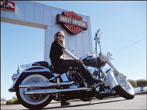 TONY CAMPBELL/Route 66 Motor Sports and Mother Road Harley-Davidson<br> Jenni Coliukos shows off a classic Harley-Davidson at Route 66 Motor Sports and Mother Road Harley-Davidson in Kingman. Harley-Davidson has signed an agreement with Chrysler to use the Arizona Proving Grounds near Yucca to test its new bikes.