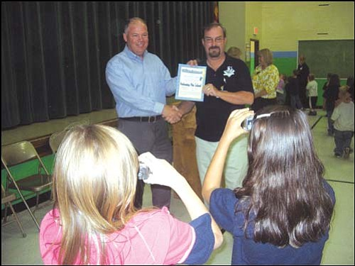 AARON ROYSTER/Miner<br> Palo Christi students Jamilynn Gonzalez (left) and Elsie Moya (right) take pictures Friday of Kingman Mayor John Salem (left) presenting Palo Christi Principal Steve Hite a certificate of achievement for obtaining performing-plus status from the Arizona Department of Education.