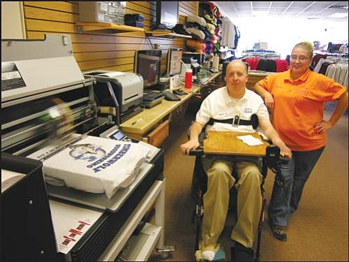 Leroy Butler Jr., seated above, is owner of Lee's Uniforms and Embroidery. He and his assistant, Billie Bear, watch closely as the store's garment printer bonds a local cabinet company's logo to a T-shirt. Butler said the company, Timberwolf Woodworking, was responsible for installing his store's numerous cabinets.  At bottom left, Bear holds a T-shirt sporting the image of Butler's twin nephews, Dylan and Evan Steadman. Butler said such custom T-shirts take only about five minutes each to produce. And, lower right, Lee's Uniforms and Embroidery is capable of embroidering or printing almost any image on any part of a baseball cap. The store carries more than 100 varieties of blank caps just waiting to be customized.<br> JAMES CHILTON/Miner