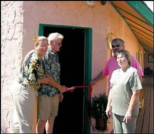 """The Journey: Renowned artist Roy Purcell (second from left) cuts the ribbon to his new art gallery in Chloride with his wife, Bev (left) as Bonnie and John McNeely, owners of Yesterday's Restaurant, look on during the opening of the art gallery. The artist of """"The Journey,"""" the internationally known paintings on the cliff side of Chloride, has continued his work near Tuscan and is ready to have a more solid presence in the town that started his life's journey. (GVG Photo/JENNIFER BARTLETT)"""