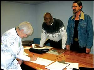 Founding mother: Peggy Cone is the first to sign the IGV incorporation petitions in Golden Valley. Looking on are IGV Chairman Henry Peairs Jr. (center) and Randy Cone, petitions sub-committee chairman. Photo: GVG Photo/DONNA NEWMAN