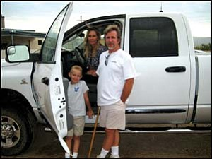 Riders on the storm: The Mathis family rode out of the July 24 Sacramento Wash floodwaters in their pickup truck, despite water broadsiding the vehicle and spraying up over the hood. GVG Photo/DONNA NEWMAN