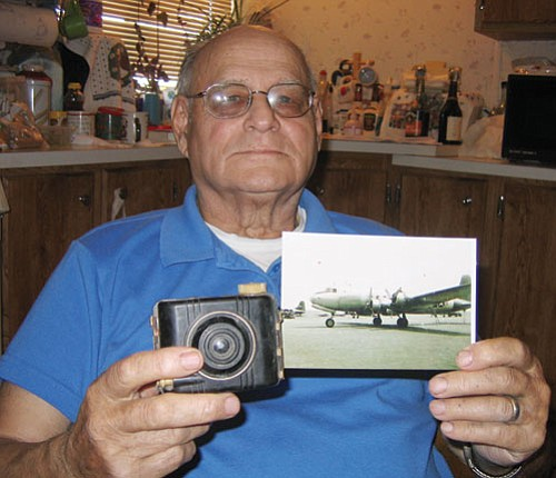 Ground support: Hank Arnold holds a photo he took of an Air Force cargo plane, the type he unloaded during the Berlin airlift. In his other hand is the Kodak Baby Brownie camera he used to shoot the picture.<br> <i>GVG Photo/TERRY ORGAN</i>