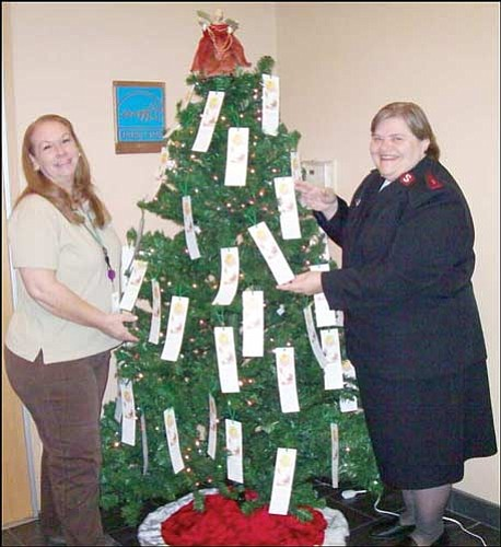 MCSO/Courtesy<br> Kelly Rhodes (left), senior office assistant, and Captain Sue Spousta of the Salvation Army arrange angel tags on the Angel Tree in the main lobby of the Mohave County Sheriff's Office, 600 W. Beale St. The tags contain gift ideas for local children in need.