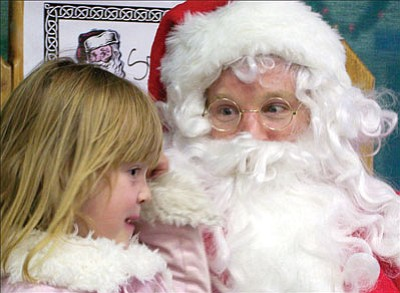Courtesy<br><br> Santa Claus talks about holiday gifts with Callie Luke, 6. He will be all over Mohave County on Tuesday as MCC Shines lighting ceremonies occur on all four campuses.