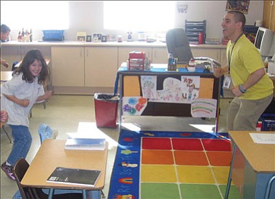 AARON ROYSTER/Miner<br><br> Kingman Regional Medical Center nutritionist and dietitian Dino Pierce (right) leads Juliana Reyes, left, and Elisa Jenkins and the rest of the second-grade accelerated class at Manzanita Elementary in exercises on Wednesday.