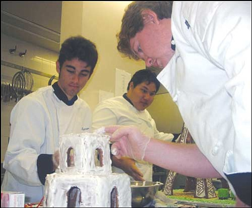 AARON ROYSTER/Miner Kingman High School senior Michael Perry (from left), junior Alex Mayo and Charles Spicer work on their Gingerbread Fantasies contest entries Friday in the school cafeteria. The entries will be judged at 10 a.m. on Saturday at Kettlehut Antiques, 308 Beale St.