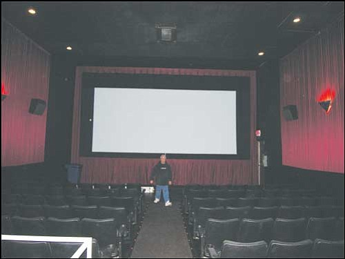 JAMES CHILTON/Miner Manager Tom Daugherty walks up the aisle Monday in one of four theaters in the Brenden Theatres Kingman Cinemas complex. The theaters will reopen with charity showings of four movies Wednesday and Thursday evenings.