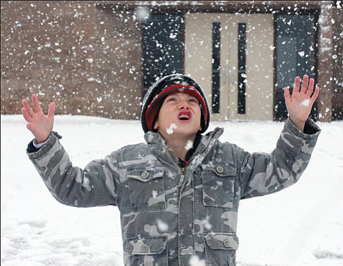 JC AMBERLYN/Miner<br><br> Sandy Ahler�s second-grade class took the opportunity to go outside briefly and play in the snow at Hualapai Elementary School Wednesday. Here, Tyler Pearson watches snowflakes fall. To view more snow day photos, visit our Photo Gallery page.