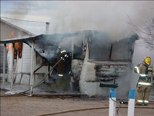 KFD/Courtesy<Br><br> Kingman firefighters combat a blaze at a mobile home in the 2200 block of Emerson Avenue on Friday.