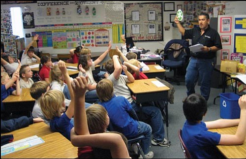 AARON ROYSTER/Miner Kingman Academy of Learning Intermediate fourth-graders show they know about the recycling symbol when Kingman Sanitation Supervisor Ed Tapia asks on Wednesday.