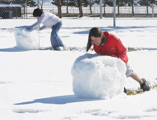JC AMBERLYN/Miner Sarah and Phillip Ponce roll up snowmen at Centennial Park Tuesday afternoon.