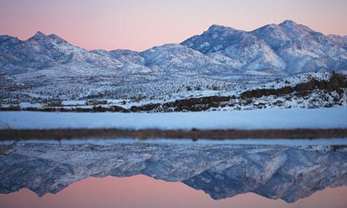 JC AMBERLYN/Miner<br><br> The Hualapai Mountains are reflected in a puddle along Andy Devine Avenue Tuesday evening.