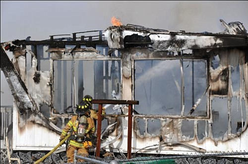 BUTCH MERIWETHER/Courtesy<br><br> Firefighters with the Northern Arizona Consolidated Fire District No. 1 hose down a flaming double-wide mobile home in the 4600 block of Glen Road on Thursday.