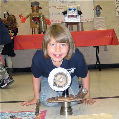 AARON ROYSTER/Miner<br><br> Manzanita Elementary first-grader Nolan Robertson poses for Inventors' Day in the school gym Friday with Rusty, her robot.