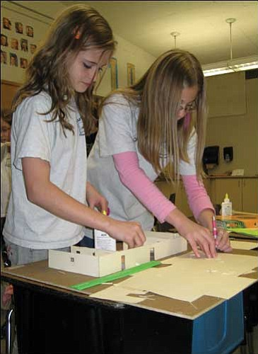 """AARON ROYSTER/Miner Manzanita fifth-grader Mariah Dreer (left) places an interior wall on a model home while her classmate Lydia Kiriakidis shapes another wall on Tuesday in Scott Taylor's classroom. The class project """"Ours by Design"""" teaches the students math through construction of complete scale homes created by the students."""