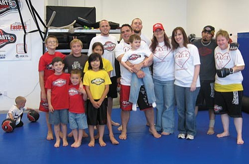 JEN MILES/Courtesy<Br><Br> Members of Parenting Autism Challenges Together and Champion Mixed Martial Arts pose during the Knock Out Autism fundraiser on March 21 at CMMA, 2505 Hualapai Mountain Road, Suite D.
