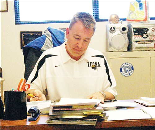 SHAWN BYRNE/Miner<br><Br> Kingman Academy's athletic director Eric Lillis handles some paperwork in his office at KAHS on Wednesday. Lillis will leave KAHS after six years to become the next principal at Kingman Academy of Learning Intermediate School in the fall.