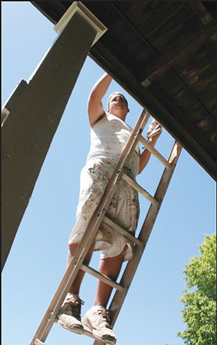JC AMBERLYN/Miner<br> Robbie Hooper of Sanderson Painting works on the Bonelli House Wednesday.