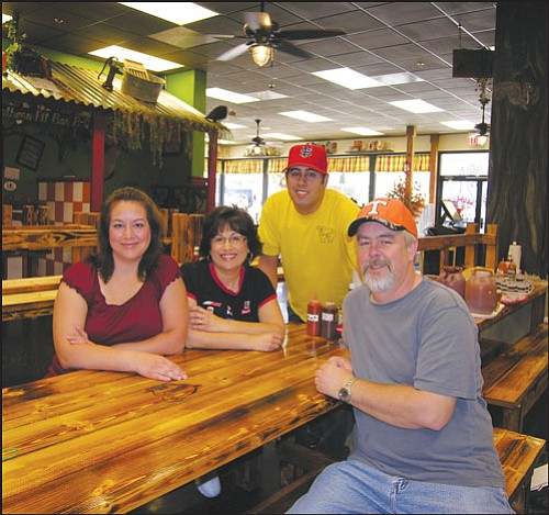 JAMES CHILTON/Miner<br> One smokin' family: Meet the faces behind the food – from left to right: Daughter Talisha Mastin, mother Tammy Floyd, son Brandon Floyd and father Bubba Floyd sit on a park bench inside Rednecks Southern Pit BBQ, 420 E. Beale St., Friday morning.