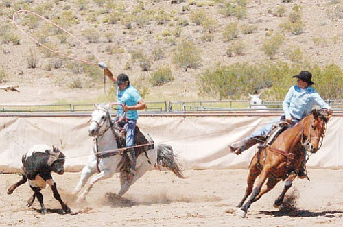 "SHAWN BYRNE/Miner<br><Br> Ty Riddell (left) and Kingman High's Ray ""Huckleberry"" Sandsness work together in team roping at the yearly fundraiser for the KHS FFA and Rodeo Club Saturday in Kingman. The club earned $5,200 by holding the 11th Annual Kingman FFA roping competition."
