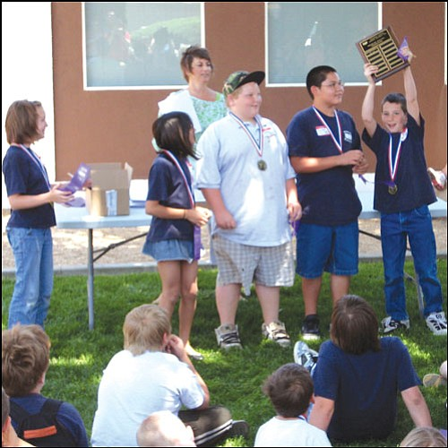AARON ROYSTER/Miner<br> La Senita Elementary student Ed Corbin (right) lifts up the problem solving plaque on Thursday while Kingman Unified School District Curriculum Director Mary Ann Smith (background) and teammates (from left) Samantha Hoover, Dakota Huff, Brenden Blanchard and Jared Quinonez look on. The team won the traveling plaque at the 2009 Mental Math Competition at Manzanita Elementary.
