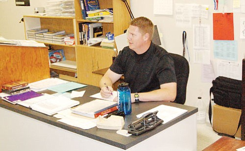 SHAWN BYRNE/Miner<br><br> Kingman High's new football coach Rob York works at his desk in his science classroom at KHS. York, a 1999 graduate of KHS, takes over the Bulldogs after Jamie Nelson's one-year stint with the team.