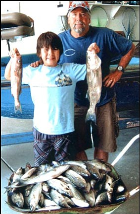 DON MARTIN/For the Miner<br> 12-year-old Jake Cave and his father, John Cave, show the fish caught during an overnight fishing trip out of South Cove on Lake Mead with AZ Hunter Education Chief Instructor Don Martin. The trio caught 101 stripers and four channel catfish.