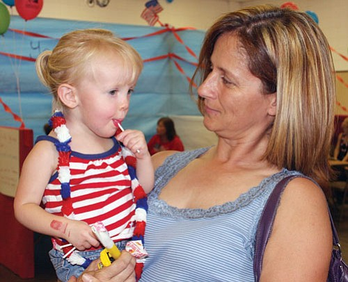 The annual 4th of July Festival was held at Mohave County Fairgrounds Saturday. There were various contests, including a talent show, Little Miss Firecracker and Little 4th of July contests and other activities. Here, Shelli Whaley holds her granddaughter, Katelyn Hoffman, who enjoys a lollipop.