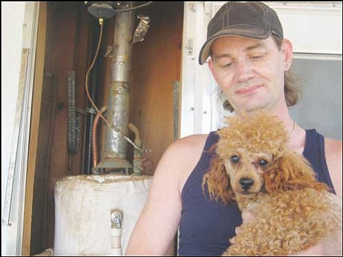 ERIN TAYLOR/ Miner<br> Mike Webb holds his poodle, Rusty, in front of the gas water heater that almost burned down the family's mobile home recently.