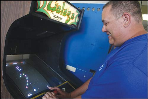 JC AMBERLYN/Miner<br> Adam Arendt, owner of Game On Arcade, plays Galaga Wednesday morning. Arendt says he opened the arcade to give kids here something to do.
