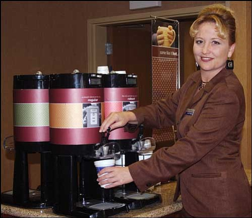 Stephani Bass, general manager of Hampton Inn and Suites in Kingman, gets a cup of coffee Wednesday at the hotel's dining area. Unlike 10 local hotels cited by the county Department of Public Health recently, Hampton Inn has the required type of sink to serve food to guests.
