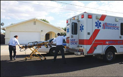 JC AMBERLYN/Miner<br> River Medical Ambulance personnel prepare to pick up the 911 caller Wednesday on Davis Avenue. It took Kingman Police and dispatchers over an hour to ascertain who the distressed caller was and where he lived.