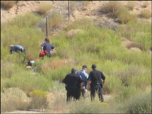 ERIN TAYLOR/Miner<br> Police photograph the scene where Carlos Sai was found dead Thursday on the south side of Interstate 40 just east of the ramp at Andy Devine Avenue.