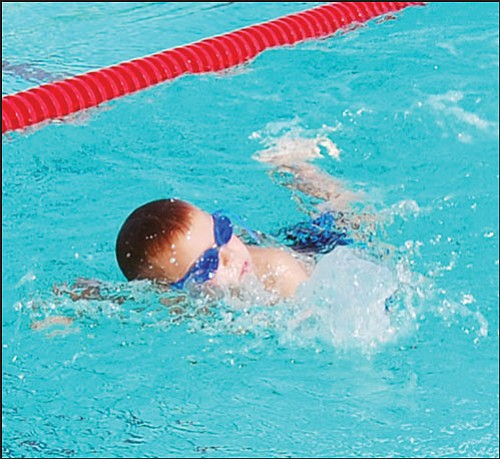 """SHAWN BYRNE/Miner Kingman Dolphins' Gabriel Otero swims toward the finish in the boys 8-and-under 25-yard freestyle in the Kingman Andy Devine Invitational Saturday at Centennial Park. Five teams with more than 100 swimmers competed in the annual event. <b><a href=""""Formlayout.asp?formcall=userform&form=20""""target=""""_blank"""">Click here to purchase this image as a print or photo gift</a></b>"""