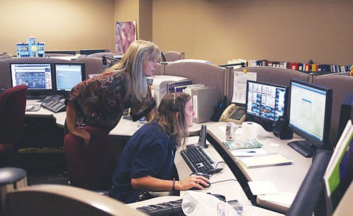 "JC AMBERLYN/Miner<br><br> Anita Mathers, seated, dispatch training officer at Mohave County Sheriff's Office Dispatch Center, answers a call Wednesday. Dispatch Supervisor Jody Schanaman stands behind her. <a href=""Formlayout.asp?formcall=userform&form=20""target=""_blank"">Click here to purchase this photo</a>"