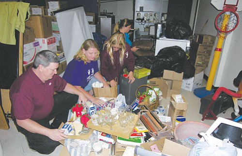 "JAMES CHILTON/Miner<br><br> Members of the Kingman Middle School Band Boosters organize donated items they plan to sell at a rummage sale Saturday. Pictured from left to right are: Don Gragg, Toni Henry, KMS band student Taylor Boom and her mother, Sharahn. <a href=""Formlayout.asp?formcall=userform&form=20""target=""_blank"">Click here to purchase this photo</a>"