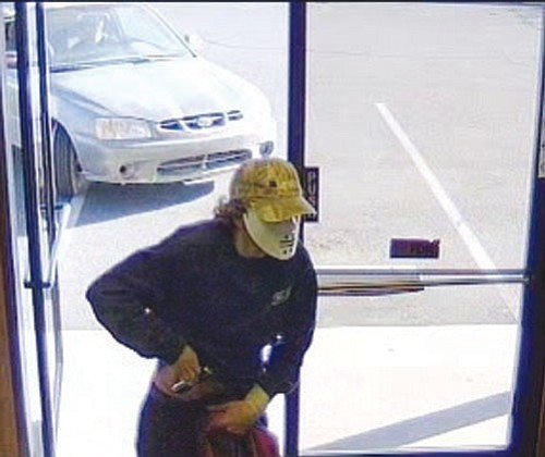 Courtesy<Br><BR> A masked gunman reaches for a weapon as he enters National Bank of Arizona Friday afternoon. The car used in the crime, with someone in the driver's seat, is visible in the background.