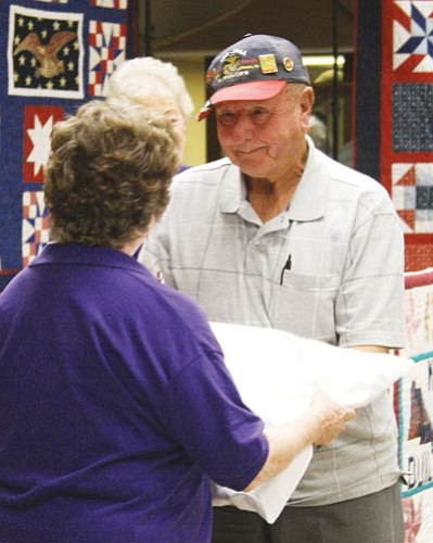 "Margie Huber presents a Quilt of Valor to Al C. Eutsey Jr. Eutsey, a Marine, served on Iwo Jima during World War II.<BR><a href=""Formlayout.asp?formcall=userform&form=20""target=""_blank"">Click here to purchase this photo</a>"