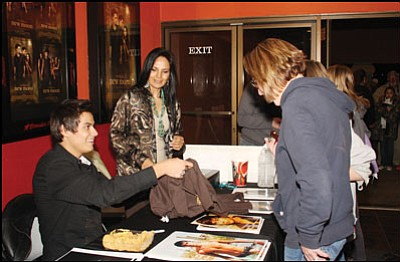"JC AMBERLYN/Miner<br> Kiowa Gordon hands a ""Twilight"" shirt to a fan Monday night at Brenden Theatres. His mother, Camille Nighthorse, watches. More than 500 people waited in line to see him. <b><a href=""http:kingmandailyminer.com/Formlayout.asp?formcall=userform&form=20"">Click here to purchase this image as a print or photogift</a></b>"