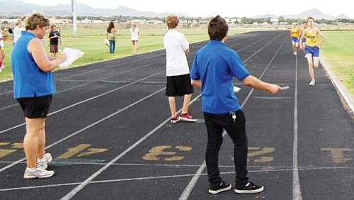 "SHAWN BYRNE/Miner<Br> Kingman High's cross country, and now track, coach Anne Bathauer, left, records her team's times during a meet against Valley Vista and Mohave in September.  <a href=""http://kingmandailyminer.com/Formlayout.asp?formcall=userform&form=20"">Click here to purchase this photo</a>"