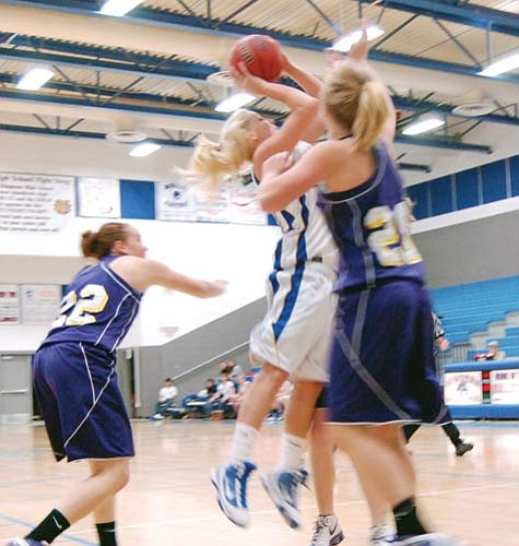 "SHAWN BYRNE/Miner<br> Kingman High's Lindsey Reed goes up against two Havasu defenders Dec. 8 at KHS. Reed scored 25 points Saturday as the Lady Bulldogs took third place at the Schuck Component Shootout Invitational in Glendale.  <a href=""http://kingmandailyminer.com/Formlayout.asp?formcall=userform&form=20"">Click here to purchase this photo</a>"